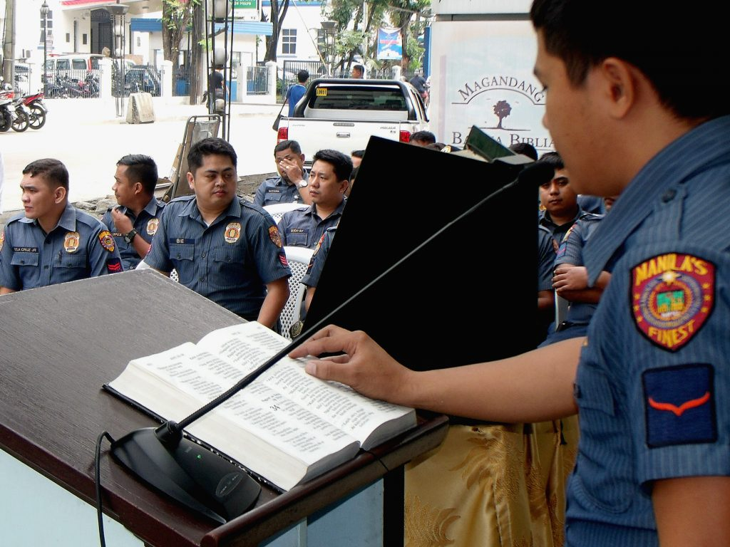 An officer from the Manila Public District reads Bible verses during a public Bible reading.
